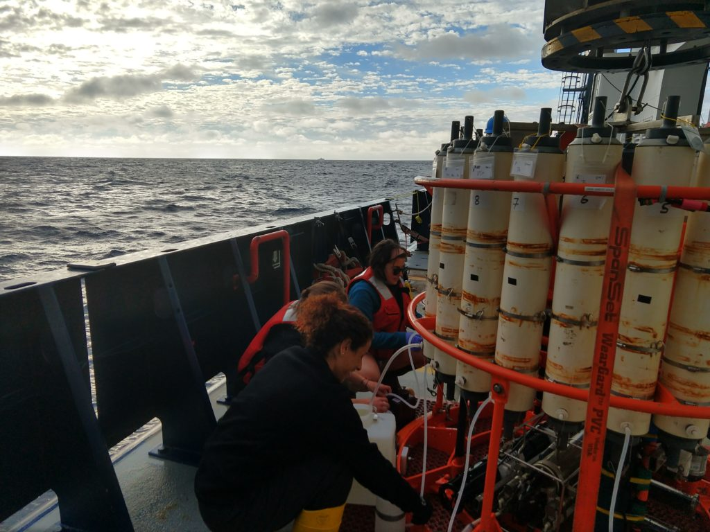 Dr. Claudia Benitez-Nelson (University of South Carolina), my mentor on ship, sampling water at the sunrise Conductivity, Temperature, and Depth CTD cast. Credits: Abigale Wyatt