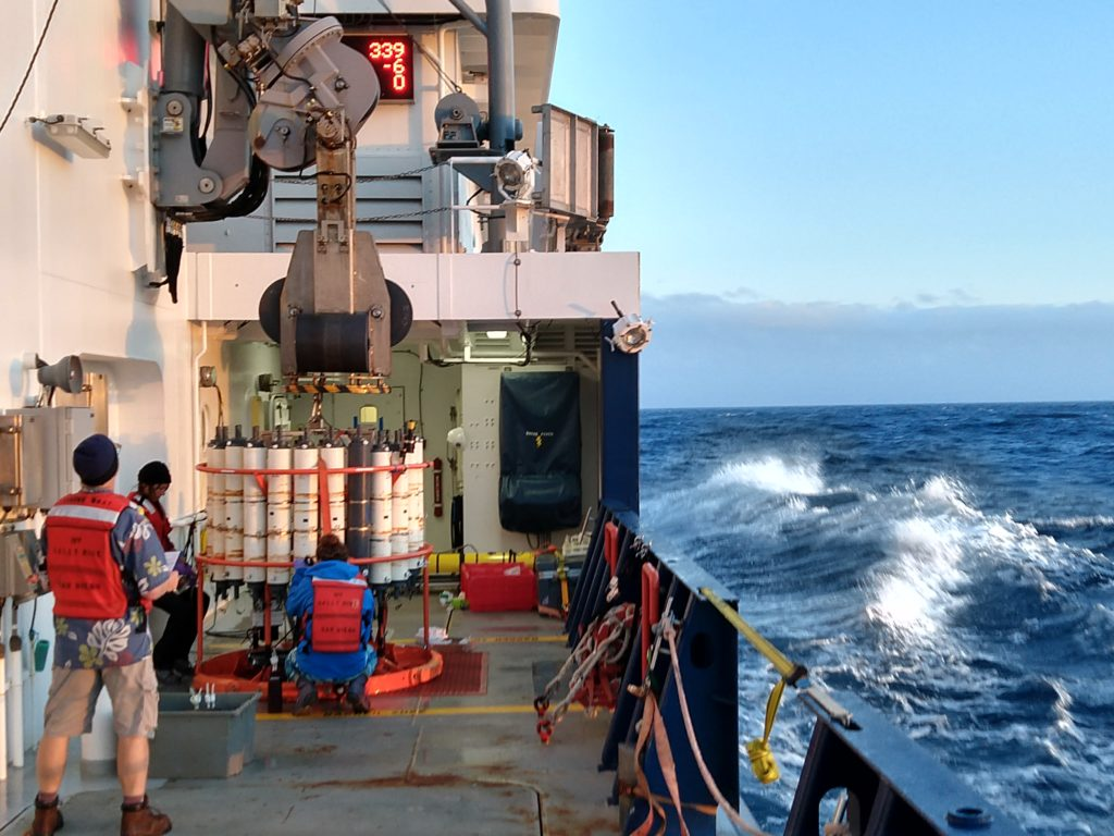 Even as the R/V Sally Ride steams ahead to the next station, scientists are on deck collecting water from the last Conductivity, Temperature, and Depth (CTD) cast. Credits: Abigale Wyatt