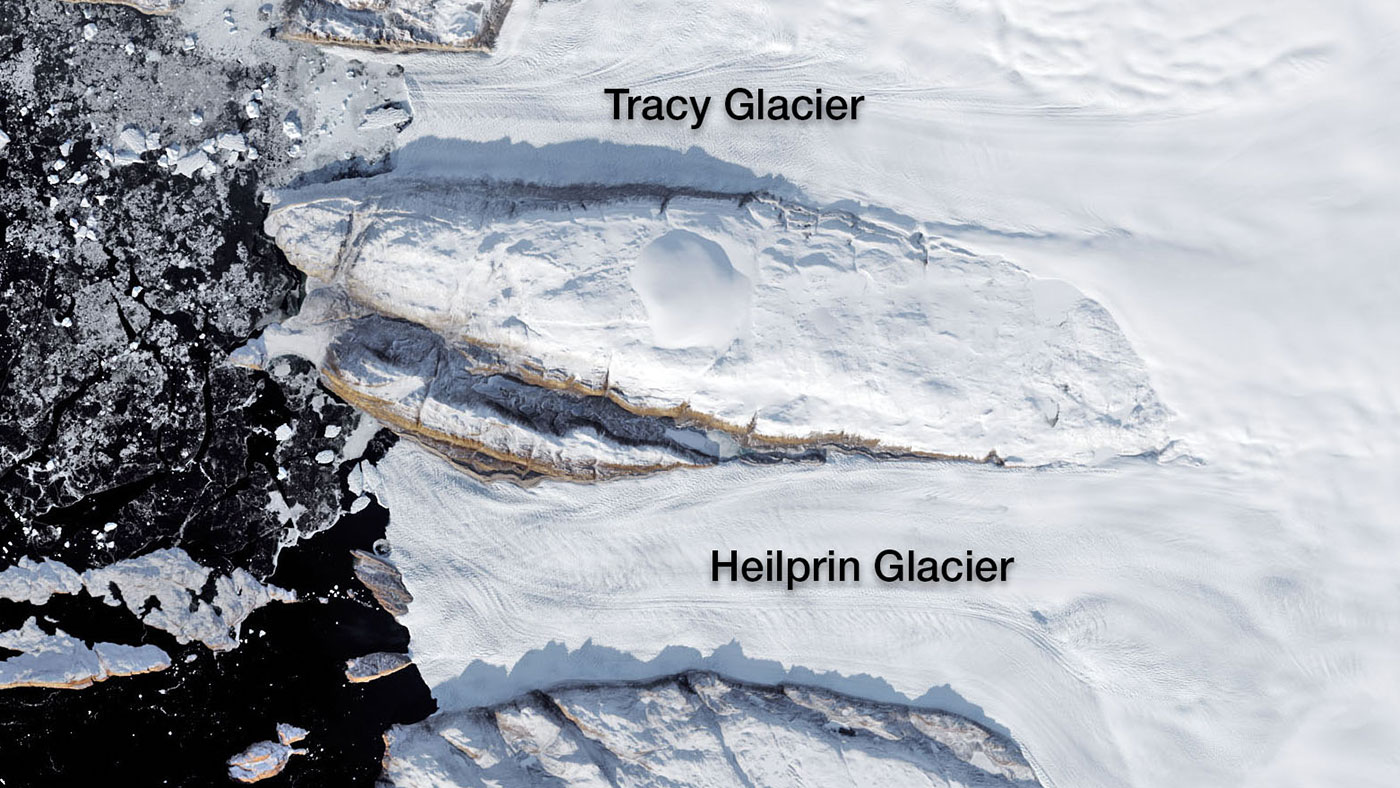 Tracy and Heilprin glaciers in northwest Greenland. The two glaciers flow into a fjord that appears black in this image. Credit: NASA